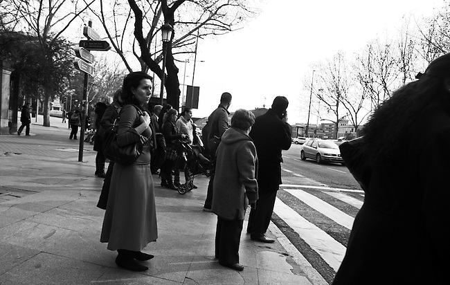 Pedestrians wait at a crosswalk in Madrid, Spain. Feb. 20, 2009.