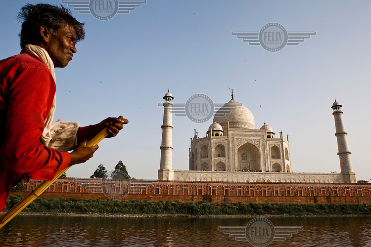 A boatman rows on the Yamuna River passing by the 17th Century Taj Mahal .