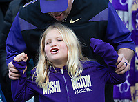 A young Dawg fan gets some help from Dad while cheering on the Huskies.