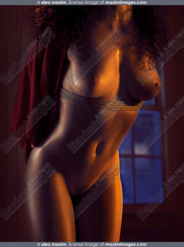 Beautiful nude woman body with shiny skin and bondage ropes in dim dramatic light