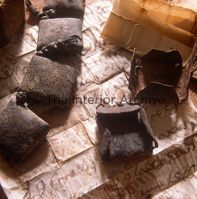 Small leather pouches used to hold folded paper with handwritten messages.