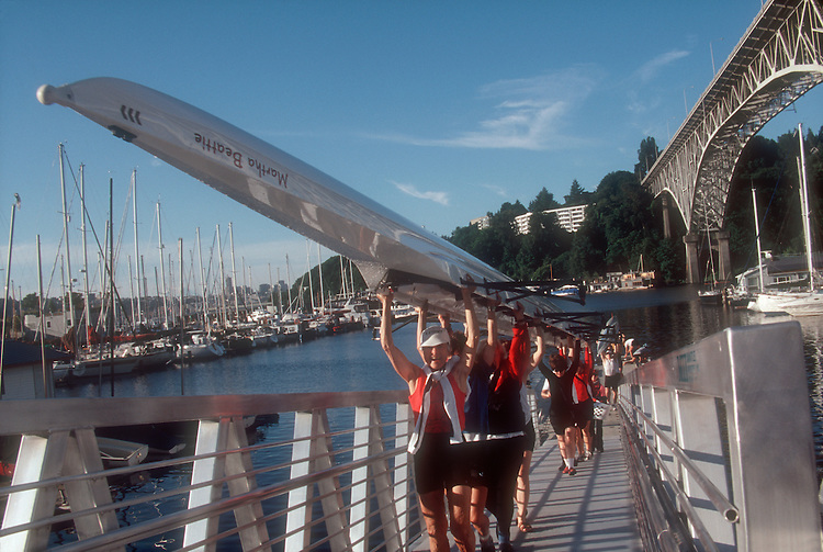 Seattle, Senior women rowers carrying an eight-oared rowing shell into the boathouse, Martha's Moms Rowing Club, Washington State, Pacific Northwest, USA,