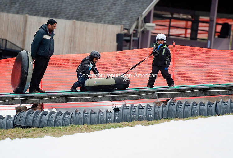WOODBURY, CT--- -122615JS03--A family makes their way up the conveyer belt to the top of the hill for some tubing fun Saturday at the Woodbury Ski Area in Woodbury. The facility has man-made snow in areas for tubing, skiing and snowboarding.<br /> Jim Shannon Republican-American