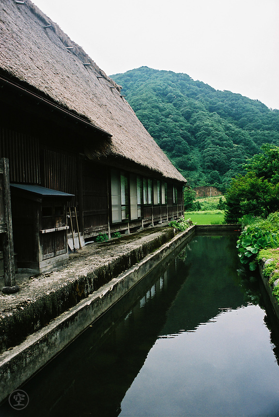 Detail of a traditionally house and bordering moat-style fish pond in the preserved town of Gokayama, Japan.