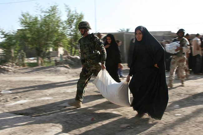 An Iraqi soldier helps a woman in Baqubah, Iraq carry a bag of rice as U.S. and Iraqi soldiers distribute emergency food supplies to local residents caught in fighting between the troops and insurgents. June 24, 2007. DREW BROWN/STARS AND STRIPES