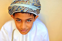 Oman, Muscat, close-up portrait of a young boy smiling in traditional dress with hat Few years ago photographers Anthony Asael and Stepahnie Rabemiafara dreamed a dream that seemed quite imposible: to visit every country of the World promoting arts and tolerance among children and, of course, taking photographs of them. With little money and resources but an impressing will, the duo got an astonishing goal. In four years they visited 300 schools in 192 countries where kids participating of the project created 18,000 pieces of artwork. <br />