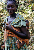 La Gongue, Gabon. Young Gabonese rural women with her baby in a sling on her back.