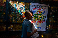"""A Colombian sign painter apprentice folds over a just-finished music party poster in the sign painting workshop in Cartagena, Colombia, 12 December 2017. Hidden in the dark, narrow alleys of Bazurto market, a group of dozen young men gathered around José Corredor (""""Runner""""), the master painter, produce every day hundreds of hand-painted posters. Although the vast majority of the production is designed for a cheap visual promotion of popular Champeta music parties, held every weekend around the city, Runner and his apprentices also create other graphic design artworks, based on brush lettering technique. Using simple brushes and bright paints, the artisanal workshop keeps the traditional sign painting art alive."""