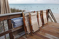 Deck chairs stacked against the wooden fence of the decked area by Vero beach