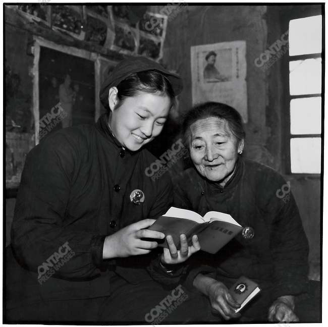 "During her ""reeducation,"" a dancer from the Heilongjiang Province Song and Dance Company learns Mao Zedong's works with an elderly peasant woman; Xinsheng Commune, Qing'an County, Heilongjiang Province. November 4, 1969. The original picture was retouched prior to publication in order to show an unobstructed and sharply focused portrait of Mao on a clean-up background."