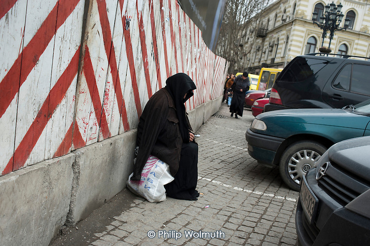 An elderly woman begs in a street in central Tbilisi, Georgia.