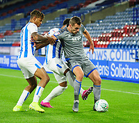 Lincoln City's Harry Toffolo shields the ball from Huddersfield Town's Juninho Bacuna, left, and Josh Koroma<br /> <br /> Photographer Andrew Vaughan/CameraSport<br /> <br /> The Carabao Cup First Round - Huddersfield Town v Lincoln City - Tuesday 13th August 2019 - John Smith's Stadium - Huddersfield<br />  <br /> World Copyright © 2019 CameraSport. All rights reserved. 43 Linden Ave. Countesthorpe. Leicester. England. LE8 5PG - Tel: +44 (0) 116 277 4147 - admin@camerasport.com - www.camerasport.com