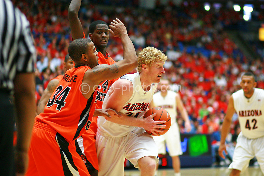 Jan 10, 2009; Tucson, AZ, USA; Arizona Wildcats forward Chase Budinger (34) is double-teamed by Oregon State Beavers guard Lathen Wallace (34) and forward Omari Johnson (24) in the second half of a game at the McKale Center.  The Wildcats won the game 64-47.