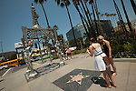 Two women take a photo of a Hollywood Walk of Fame Star at the Hollywood La Brea Gateway at the intersection of Hollywood Blvd. and La Brea Avenue. The statue is a tribute to the White, Hispanic, Asian-American and African-American women of Hollywood.  The four women represented by the statues are Mae West, Dolores Del Rio, Anna Mae Wong and Dorothy Dandridge.  Hollywood, CA