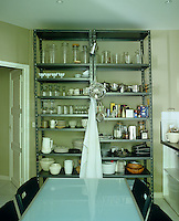 The items on the adjustable open industrial-style shelving form part of the kitchen's overall design