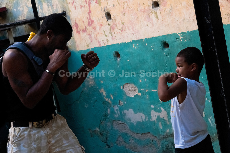 A Cuban father shows boxing techniques to his son at Rafael Trejo boxing gym in Havana, Cuba, 11 February 2010. During the last 30 years Cuba has produced more World Champions and Olympic gold medallists in amateur boxing than any other country. Many famous fighters, who came out of Cuba, were training at Rafael Trejo boxing gym in their youth. This run down open air facility in the Old Havana is a place of learning and mastering the art of boxing by the old school style. Boys begin their training very young. As sports are given a high political priority in Cuba, all children are systematically encouraged to develop their skills. Those who succeed will become heroes of Cuban society.