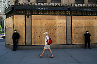NEW YORK, NEW YORK - JUNE 08: A woman walks by a boarded up Saks store on June 08, 2020 in New York City. The City began first phase of reopening after nearly three months of shutdown , also Protests continue over black Americans abuse by the Police (Photo by Kena Betancur/VIEWpress via Getty Images)