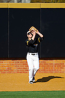 Left fielder Brandon Gonnella #11 of the Towson Tigers makes a catch on the warning track against the Minnesota Golden Gophers at Gene Hooks Field on February 26, 2011 in Winston-Salem, North Carolina.  The Gophers defeated the Tigers 6-4.  Photo by Brian Westerholt / Sports On Film