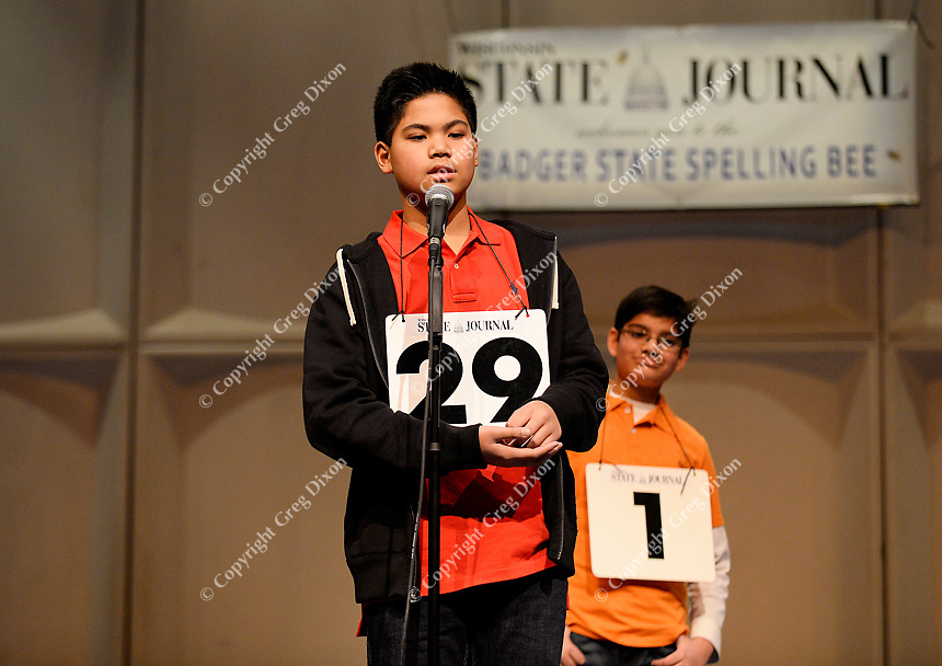 Edgewood Campus School's Martius Bautista works out the spelling of a word on his hand on his way to winning the Madison All-City Spelling Bee, as runner up, Spring Harbor Middle School's Aurush Jain, waits in line on Saturday at Madison Area Technical College's Mitby Theater