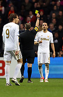 Sunday, 25 November 2012<br /> Pictured: Chico Flores of Swansea (R) sees a yellow card by match referee J Moss (C)<br /> Re: Barclays Premier League, Swansea City FC v Liverpool at the Liberty Stadium, south Wales.