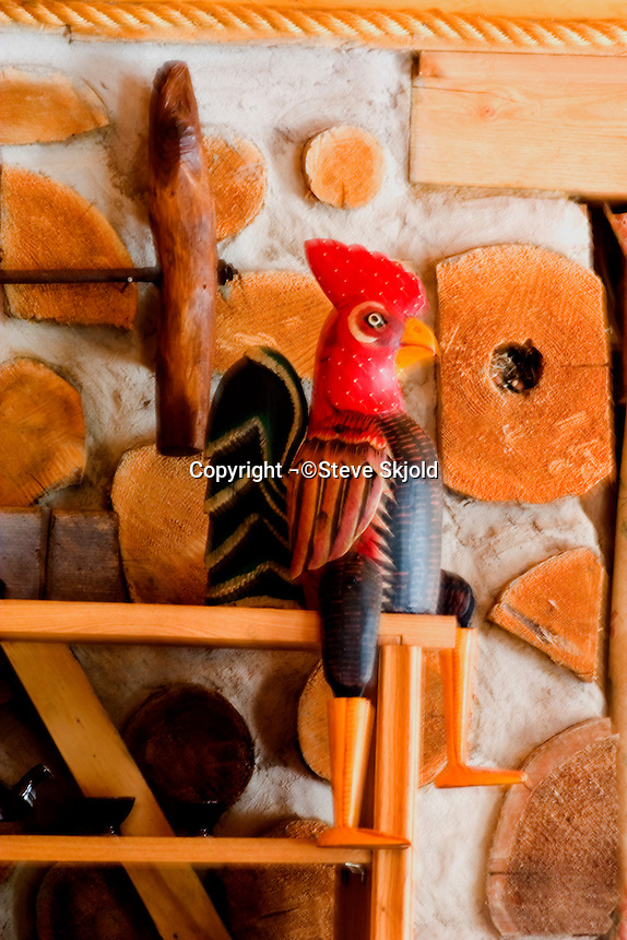 Carved jointed wooden rooster sitting on end of display case against a log embedded cement wall of a cabin.  Cable Wisconsin USA