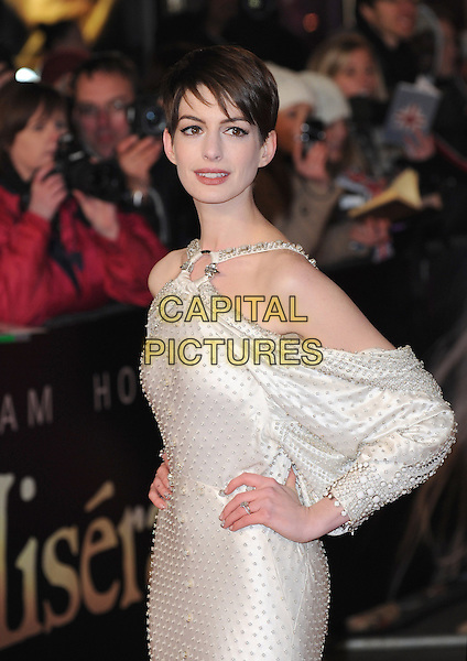 Anne Hathaway (wearing Givenchy).'Les Miserables' world film premiere, Odeon & Empire cinemas, Leicester Square, London, England..5th December 2012.half length white dress gown bejewelled sleeves satin silk draped beads beaded hands on hips batwing off the shoulder .CAP/BEL.©Tom Belcher/Capital Pictures.