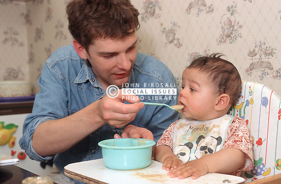 Father feeding young baby in kitchen,