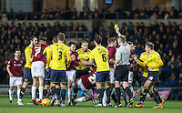 Players battle with each other as Referee Keith Hill issues a yellow card during the Sky Bet League 2 match between Oxford United and Northampton Town at the Kassam Stadium, Oxford, England on 16 February 2016. Photo by Andy Rowland.