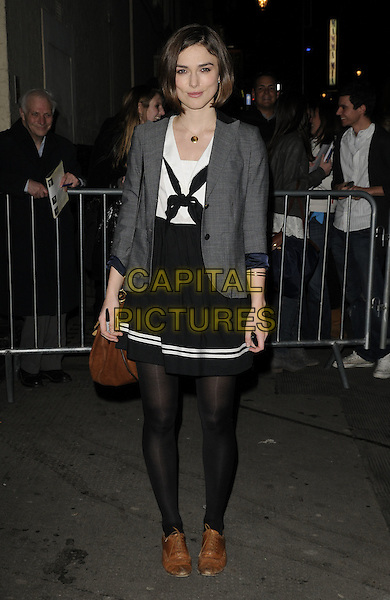 "KEIRA KNIGHTLEY.Departing from the evening performance of ""The Children's Hour"", Comedy Theatre, London, England, UK..March 23rd, 2011.full length black tights dress skirt white white stripe trim  grey gray blazer jacket brown shoes bag purse pussybow .CAP/CAN.©Can Nguyen/Capital Pictures."