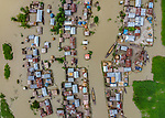 Pictured: A woman smiles as she floats through her flooded village on a raft made from banana trees.    Life carries on despite the deluge with people making the best of things amid the murky knee high water<br /> <br /> The village, which has been partially submerged for 12 days, is home to around 6,000 people.   Located on the banks of the river Jamuna, in Sariakandi Upazila, Bangladesh, the area floods yearly as a result of heavy monsoon rain. SEE OUR COPY FOR DETAILS <br /> <br /> Please byline: Abdul Momin/Solent News<br /> <br /> © Abdul Momin/Solent News & Photo Agency<br /> UK +44 (0) 2380 458800