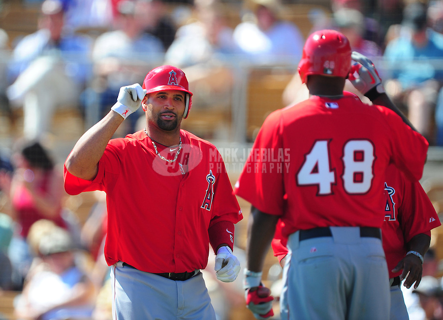 Mar. 14, 2012; Phoenix, AZ, USA; Anaheim Angels first baseman Albert Pujols (left) celebrates with outfielder (48) Torii Hunter after hitting a three run home run in the third inning against the Chicago White Sox at The Ballpark at Camelback Ranch. Mandatory Credit: Mark J. Rebilas-