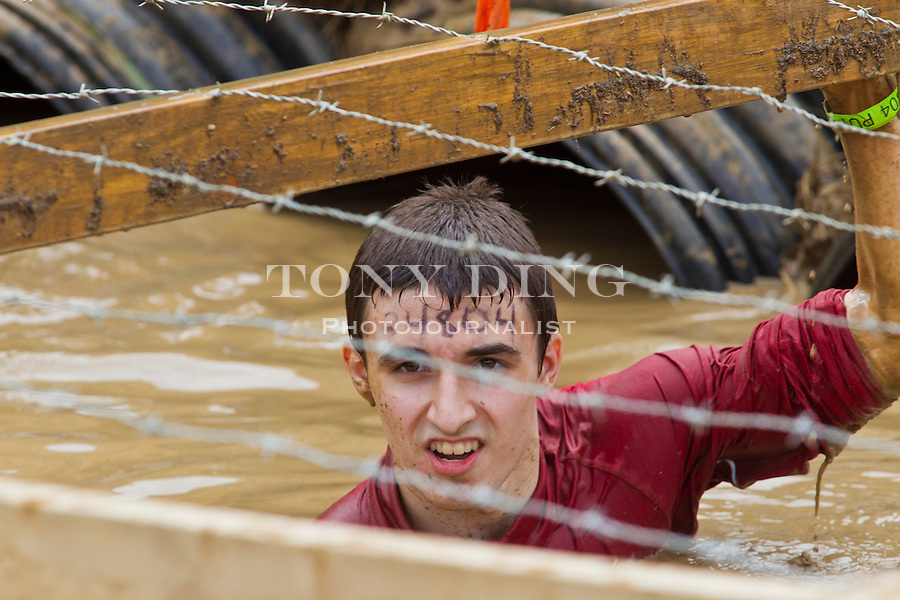 "16 April 2010: A competitor crawls through the ""Boa Constrictor"" one of twenty obstacles in the Tough Mudder adventure endurance race at Michigan International Speedway in Brooklyn, Michigan."