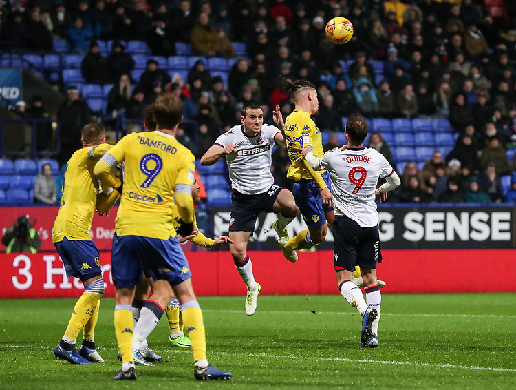 Bolton Wanderers' Jack Hobbs attacks a corner kick under pressure from Leeds United's Kalvin Phillips<br /> <br /> Photographer Andrew Kearns/CameraSport<br /> <br /> The EFL Sky Bet Championship - Bolton Wanderers v Leeds United - Saturday 15th December 2018 - University of Bolton Stadium - Bolton<br /> <br /> World Copyright © 2018 CameraSport. All rights reserved. 43 Linden Ave. Countesthorpe. Leicester. England. LE8 5PG - Tel: +44 (0) 116 277 4147 - admin@camerasport.com - www.camerasport.com