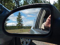 The photographer taking a photo of the Kootenay Rockies in British Columbia in car side mirror.
