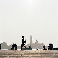 Men fishing and woman walking with a view to St Mark's Campanile, Venice, Italy