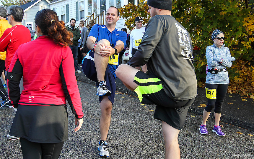 Stretching before the race, runners from left, Melissa Nowell of Hancock, ME, Mark McGunagle of Franklin, MA, and Ethan Dolleman of Medfield, MA, at the annual Seacoast Half Marathon in Portsmouth, N.H., Sunday, Nov. 10, 2013.  (Portsmouth Herald Photo Cheryl Senter)