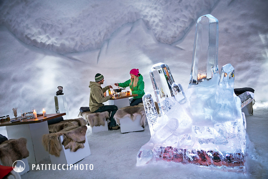 Couple eating fondue. This igloo, at the Engstligenalp, just above Adelboden Switzerland, is a popular evening fondue restaurant where diners enjoy a  night of fondue surrounded in ice sculptures.