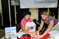 Michelle Akers autographs one of her jerseys that was auctioned off for charity during the Women's Professional Soccer (WPS) All-Star Game at KSU Stadium in Kennesaw, GA, on June 30, 2010.