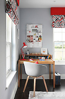 A desk area in the corner of a child's bedroom is furnished with a wooden desk and chair, a cheerful red angle-poise lamp and a pinboard, while patterned blinds brighten up the sash windows overlooking the Bedfordshire countryside