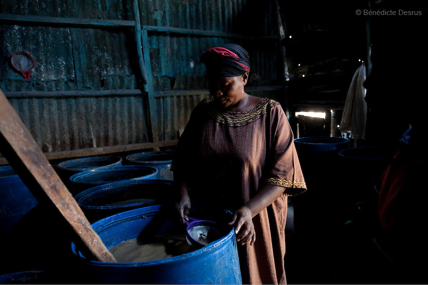 Jane, the owner of the Madiaba Busaa Club, is sieving the burned maize from  the fermenting Busaa at the Madiaba Busaa Club in a Nairobi slum on April 19, 2013. Jane has been brewing Busaa for 22 years. She opened the Madiaba Busaa Club in 1991. Busaa is a traditional fermented beer made by crudely fermenting maize, millet, sorghum or molasses. At Kshs 35 per liter it is much cheaper than a Kshs120 half-liter bottle of commercial beer. The local brew was legalised in 2010 and since then busaa clubs have become increasingly popular. Drinking is on the rise in Kenya, especially among young people. Photo by Benedicte Desrus