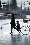 Zorg en Arbeid, Woon- werkverkeer: Ouders brengen hun kinderen naar school. COPYRIGHT TON BORSBOOM<br /> <br /> <br /> fiets, fietsen, zorg, arbeid, ouder, ouders, ouderschap, vader, moeder, kinderen, kind, dochter, school, werk, arbeid, rolverdeling, verkeer, risico, regen, brengen, meelopen