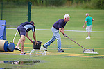 © Joel Goodman - 07973 332324 . 28 July 2013 . Rochdale Cricket Club , Bridgefold Road , OL11 5BX , UK . Working against the rain , groundsmen try to clear the pitch but rain ultimately stops play between Rochdale and Clifton CC . Photo credit : Joel Goodman