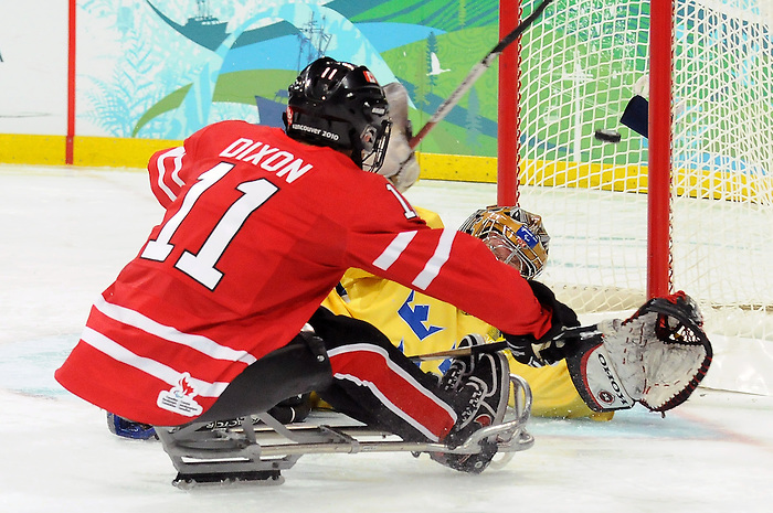 Adam Dixon (11) fires this puck past the Swedish netminder during 2010 Paralympic Games sledge hockey action at UBC Thunderbird Arena in Vancouver. Credit: CPC/HC/Matthew Manor.