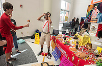 NWA Democrat-Gazette/ANTHONY REYES &bull; @NWATONYR<br /> Nick Coulter (left) Springdale High School sophomore tries to master the balero toy Monday, Nov. 2, 2015 as Manuel Garcia, Springdale junior, look on during a Day of the Dead celebration at the school. Garcia was eduating people on his alter to Roberto G&oacute;mez Bola&ntilde;os a poplular Mexican entertainer who died in 2014. The event also featured a mural that encouraged students to write what they wanted to do before they died on and there were several altars prepared for different figures in history. The Day of the Dead holiday focuses on gatherings of family and friends to pray for and remember friends and family members who have died, and help support their spiritual journey.