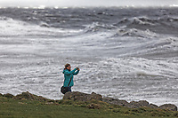 A woman takes pictures of the raging sea in Porthcawl, caused by Storm Freya in south Wales, UK. Sunday 03 March 2019