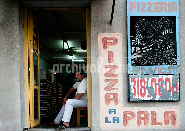 A man sits in his Pizzeria as he waits for customers  in Montevideo, Uruguay. Matilde Campodonico/Archivo Latino