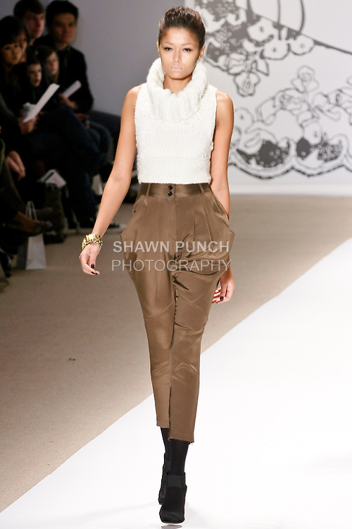 Arlene walks the runway in a chunky knit cropped turtleneck sweater in white, nostalgia ankle pant in olive, with gold and silver bracelet, by Wenlan Chia, for the Twinkle By Welan Fall 2010 fashion show, during Mercedes-Benz Fashion Week Fall 2010.