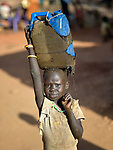 A girl carries water in a camp for over 5,000 internally displaced persons in an Episcopal Church compound in Wau, South Sudan. Most of the families here were displaced by violence early in 2017, after a larger number took refuge in other church sites when widespread armed conflict engulfed Wau in June 2016.<br /> <br /> Norwegian Church Aid, a member of the ACT Alliance, has provided relief supplies to the displaced in Wau, and has supported the South Sudan Council of Churches as it has struggled to mediate the conflict in Wau.