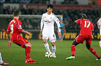 SWANSEA, WALES - MARCH 16: Ki Sung Yueng of Swansea (C) marked by Alberto Moreno (L) and Mamadou Sakho (R) of Liverpool during the Premier League match between Swansea City and Liverpool at the Liberty Stadium on March 16, 2015 in Swansea, Wales