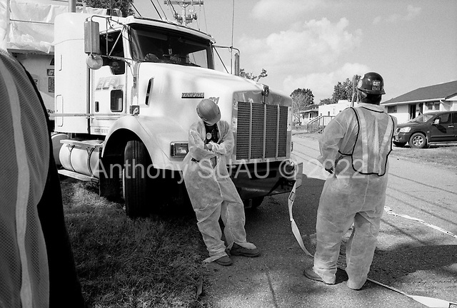 Saint Bernard's Parish, Louisiana.May 26, 2006..Demolition teams work at leveling as many as 6,000+ homes in St. Bernard's Parish damaged by hurricane Katrina in August of 2005...FEMA is offering to destroy home for free up until June 30, 2006. About 12 homes are being demolished a day so far. Waiting for everything to be in place before beginning - sometimes workers wait hours for others to come to the site...Workers are outfitted in special clothing and masks and water is poured on to the debris as the homes have asepses. The water is to keep down the asepses fumes.